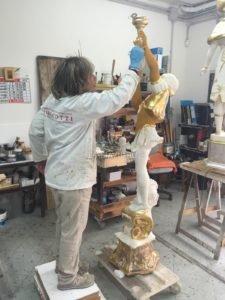 Итальянский мастер наносит позолоту на скульптуру
